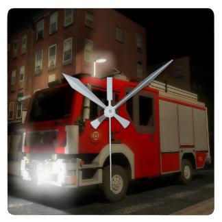 Lastkraftwagen des Feuerwehrs durch eine Straße Quadratische Wanduhr