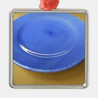 Leere Farbblaue Keramikplatte auf Strohpapier Quadratisches Silberfarbenes Ornament
