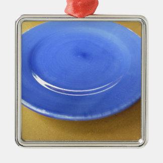 Leere Farbblaue Keramikplatte auf Strohpapier Silbernes Ornament