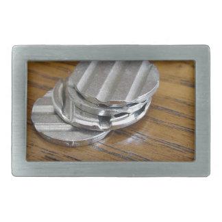 Leere metallische Münzen auf hölzerner Tabelle Rechteckige Gürtelschnalle