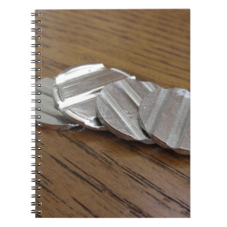 Leere metallische Münzen auf hölzerner Tabelle Spiral Notizblock