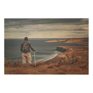 Mann an den Hochs die Landschaft erwägend Holzwanddeko