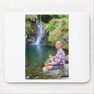 Mann, der auf dem Felsen meditiert nahe Wasserfall Mousepad