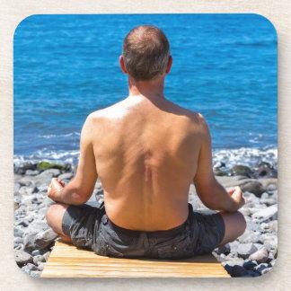 Mann, der in Strand und Meer meditiert Getränkeuntersetzer