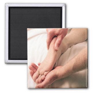 Mann, der männlichen Fuß massiert Quadratischer Magnet