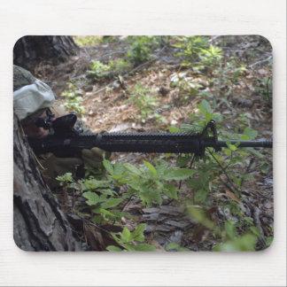 Marinesoldat benutzt einen Baum für Abdeckung und Mauspad