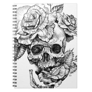 Menschliches Zeichnen des Schädels und schwarzes Notizblock