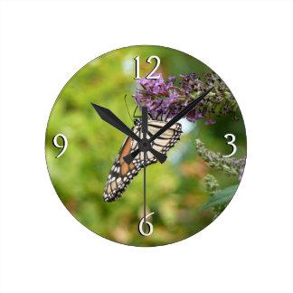Monarch-Schmetterling auf lila Schmetterling Bush Runde Wanduhr