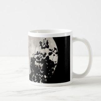 Mond hinter dunklem Blätter Kaffeetasse