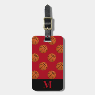 Monogramm-Brown-Basketball-Bälle auf dunkelrotem Gepäckanhänger