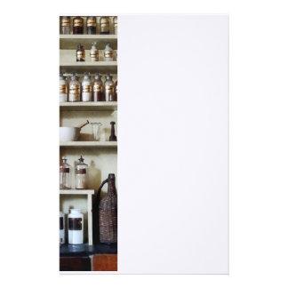 Mörser und Stampfe und Flaschen auf Regalen Briefpapier