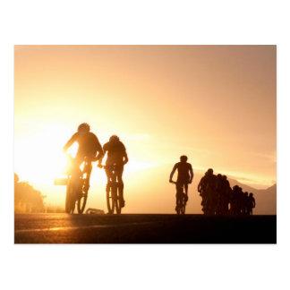 Mountainbike-Reiter machen ihre Weise über der Postkarte