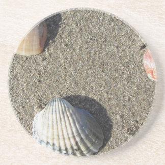 Muscheln auf Sand. Sommerstrandhintergrund Getränkeuntersetzer
