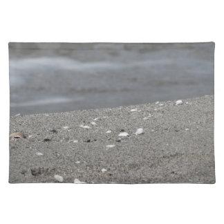 Nahaufnahme des Sandstrandes mit Meer verwischte Stofftischset