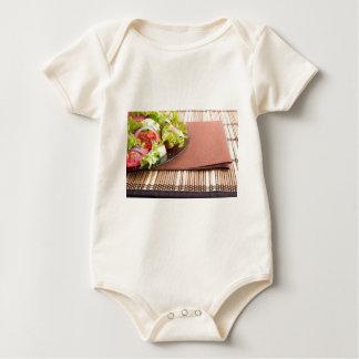 Nahaufnahmeansicht einer Platte mit frischem Salat Baby Strampler
