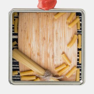 Nahrungsmittelhintergrund mit dünnen Spaghettis Quadratisches Silberfarbenes Ornament