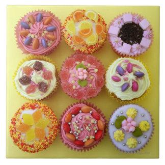 Neun kleine Kuchen jeder verziert mit Süßigkeit in Große Quadratische Fliese