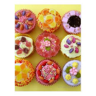 Neun kleine Kuchen jeder verziert mit Süßigkeit in Postkarten