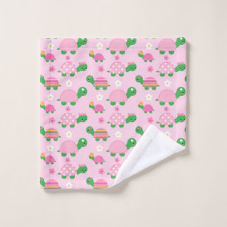 Niedliche grüne Schildkröte auf buntem Rosa Waschlappen