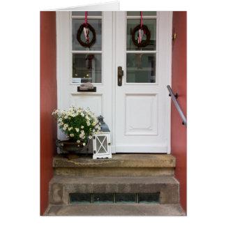 Niedliche Hütten-Tür mit einer Lampe und Blumen Grußkarte