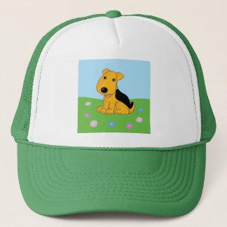 Niedlicher Airedale-Welpen-Hund im Truckerkappe