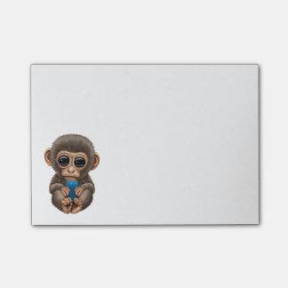 Niedlicher Baby-Affe, der ein blaues Post-it Klebezettel