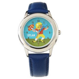 Niedlicher Fußball-Junge mit Sturzhelm scherzt Uhr