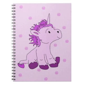 Niedlicher kleiner Unicorn auf einem rosa Spiral Notizblock