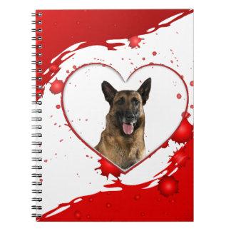 Niedlicher Schäferhund-Hund innerhalb des roten Spiral Notizblock