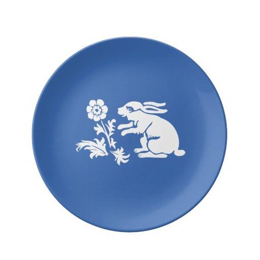 Niedliches Häschen-Kaninchen in Blauem und in Porzellanteller