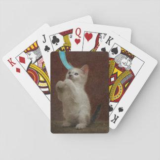 Niedliches weißes Kätzchen, das mit blauem Band Spielkarten
