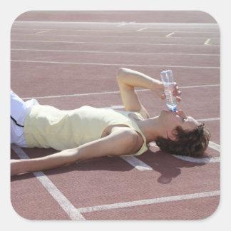 Olympischer Athlet 2012, der nach Rennen trinkt Quadrataufkleber