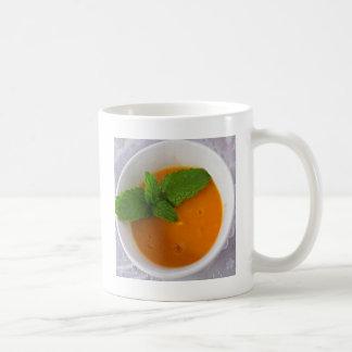 orange Bananenmango Smoothie mit grüner Kaffeetasse