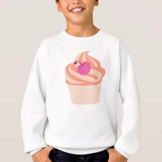 Orange kleiner Kuchen mit rosa Kirsche und orange Sweatshirt
