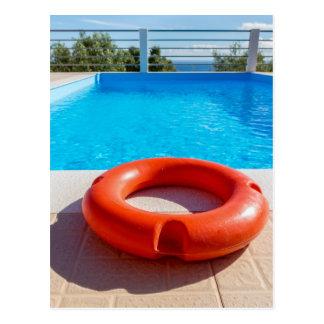 Orange Lebenboje am blauen Swimmingpool Postkarte