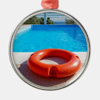 Orange Lebenboje am blauen Swimmingpool Rundes Silberfarbenes Ornament