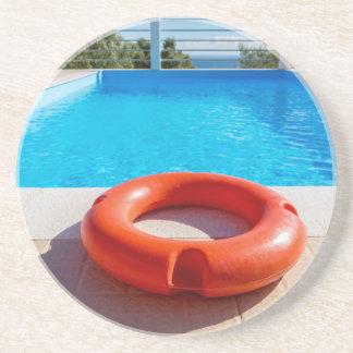 Orange Lebenboje am blauen Swimmingpool Untersetzer