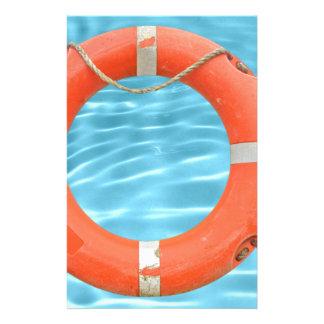 Orange lifebuoy über Swimmingpool-Wasser backgroun Briefpapier
