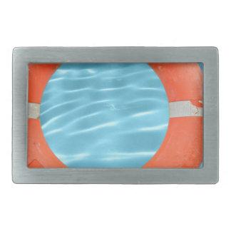 Orange lifebuoy über Swimmingpool-Wasser backgroun Rechteckige Gürtelschnalle