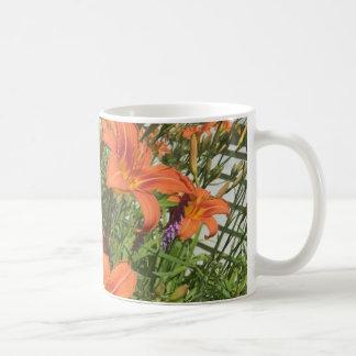 Orange Tageslilien an der Bauernhof-Kaffee-Tasse Kaffeetasse