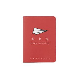 Papierflugzeug mit Monogrammreiserot Passhülle