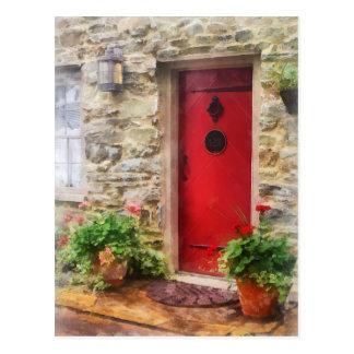 Pelargonien durch rote Tür Postkarte
