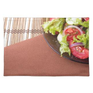 Platte mit frischem Salat der rohen Tomaten und Stofftischset