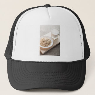 Platte mit trockenem Getreide und einem Glas Milch Truckerkappe
