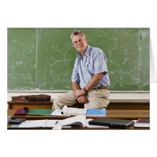 Porträt des Lehrers sitzend auf Schreibtisch vor Karte