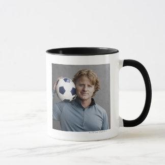 Redhead, der einen Fußball auf seiner Schulter Tasse