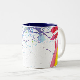 Regenbogenbürstenanschläge mit einem Spritzen der Zweifarbige Tasse