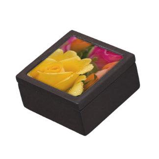 Regentropfen auf den gelb-orangeen und rosa Rosen Schachtel