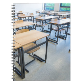 Reihen der Tabellen und der Stühle im Spiral Notizblock