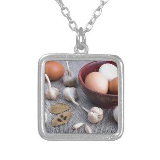 Rohe Eier und Knoblauch und Gewürze auf der Küche Versilberte Kette
